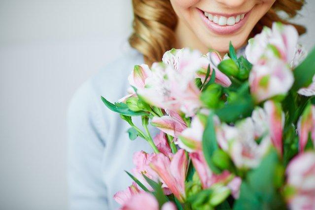 Femme qui reçoit un bouquet suite à une livraison de fleurs